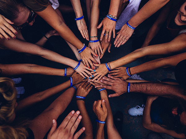 many hands in a circle together